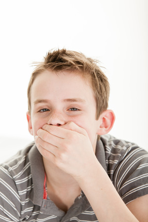 politeness: Boy wearing striped gray shirt and brown hair holds hand over his mouth stifling laughter against a white background