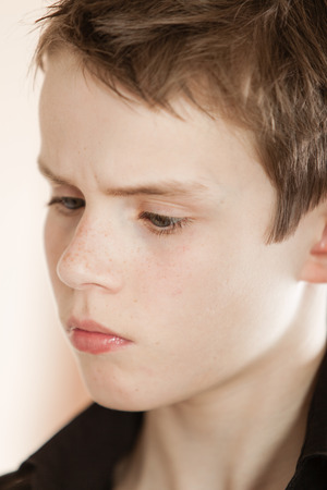 frowns: Head shot of serious boy with messy brown hair and wearing a black shirt frowns away from the camera