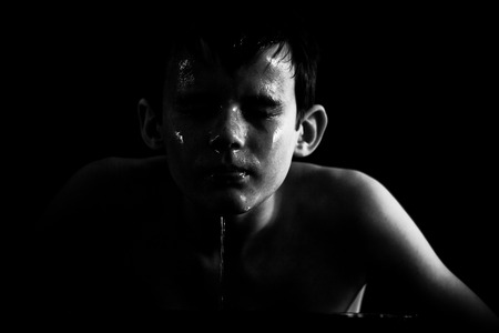 Black and white image of shirtless boy with water running down his face against a black background