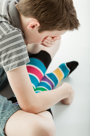 Grieving boy wearing colorful striped socks and shorts sits cross legged on the floor and covers his eyes