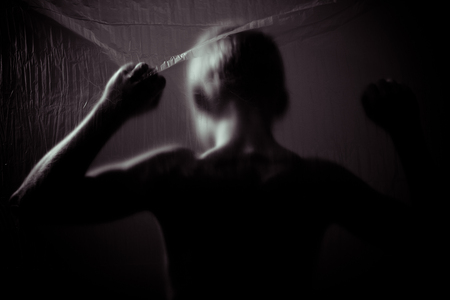 dimly: Rear view of dimly lit child with raised fist behind transparent sheet in dark, dangerous theme