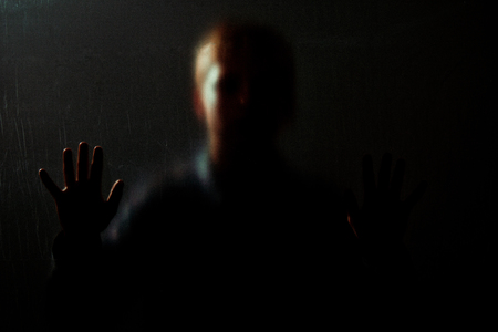 obscured: Dimly lit obscured portrait of boy surrounded by darkness and hand up in focus on transparency