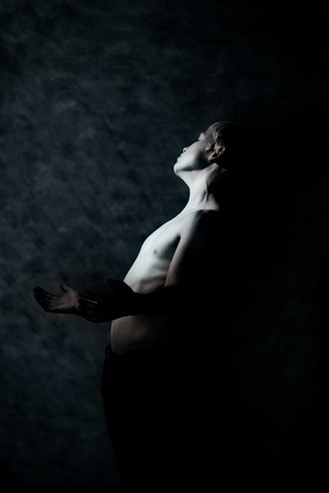 dimly: Dimly lit portrait of shirtless boy surrounded by black shadows leaning backward in pain or distress Stock Photo