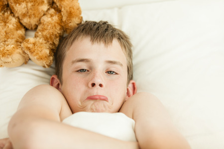 grouchy: Single pouting young teen boy laying in bed on pillow next to brown furry plush toy refusing to get up Stock Photo