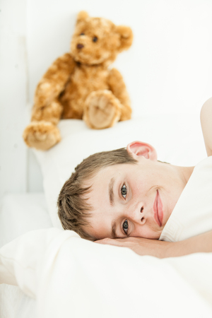 eyes open: Single smiling boy laying in bed with eyes open in front of cute fluffy plush bear above his head on pillow