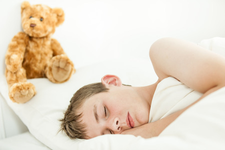 dozing: Single adorable boy sleeping with eyes closed in white sheets and blanket beside plush bear above his head on pillow