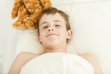 plush toy: Single grinning young teen boy laying in bed on pillow just waking up next to brown furry plush toy