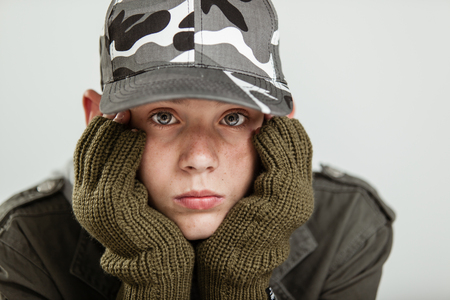 downhearted: Young boy in jacket, brown gloves and gray camouflage hat holding his pouting face in hands