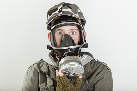 fire fighter: Close up of single male teen in jacket, brown gloves and gray camouflage hat holding a fire fighter respirator gas mask on his face