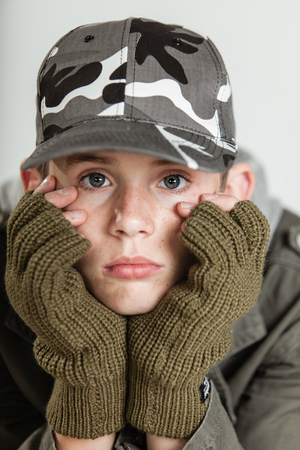 sombre: Close up of single male teen in jacket, brown gloves and gray camouflage hat holding his sulking face in hands