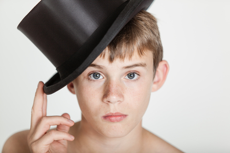 shouldered: Single bare shouldered cute male child in with serious expression tipping his black hat with two fingers Stock Photo