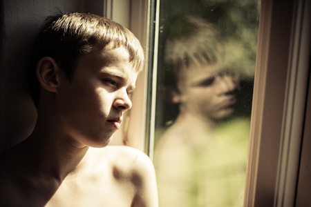 sombre: Single young sad shirtless male child leaning against wall near window with sun on one side and reflection in window