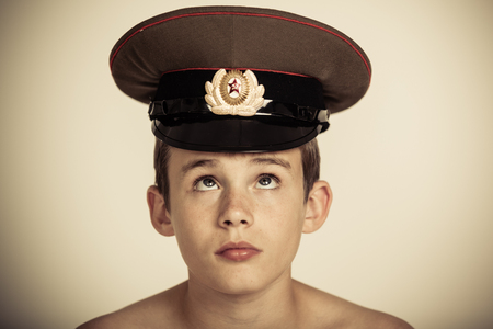 shouldered: Single bare shouldered cute male child in brown military officer hat with star badge on front and serious expression