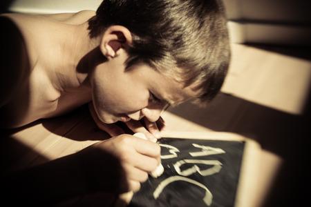 niño sin camisa: Lindo muchacho sin camisa sola escritura a, b, c, y otra palabra en tarjeta de tiza en la luz del sol