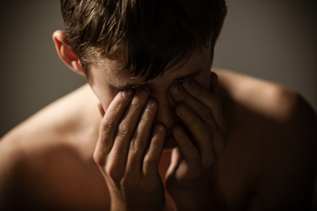 Head and Shoulders of Young Shirtless Teenage Boy Holding Face in Hands in Studio with Dramatic Lighting and Dark Background - Upset Boy Crying or Upset and Hiding Face in Hands Stock Photo