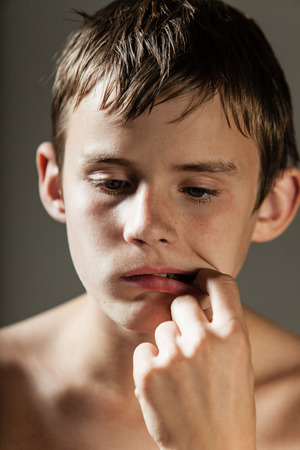 perturbed: Head and Shoulders of Young Shirtless Teenage Boy Picking Teeth with Finger and Looking Downwards in Studio with Gray Background Stock Photo