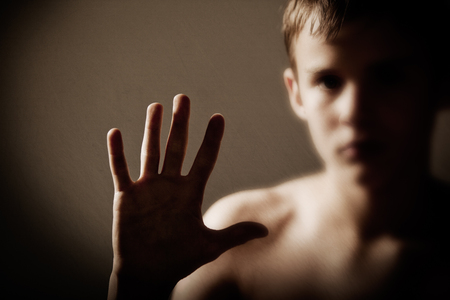 evocative: Head and Shoulders of Shirtless Teenage Boy Holding Up Hand Showing Palm to Camera with Face Out of Focus in Background in Studio with Copy Space