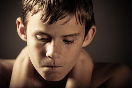 Cabeza y los hombros del joven descamisado Adolescente con las manos sosteniendo el cuello y mirando hacia abajo con expresión de enojo en Studio con fondo oscuro y el espacio de la copia Foto de archivo