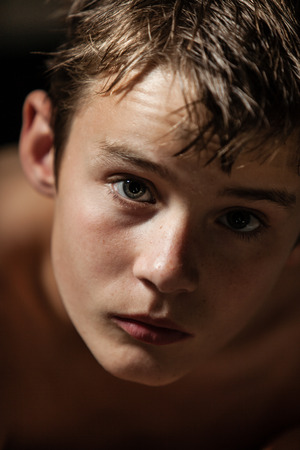 sombre: Head and Shoulders Portrait of Young Shirtless Teenage Boy Looking Up at Camera with Serious and Intense Expression in Studio with Dark Background
