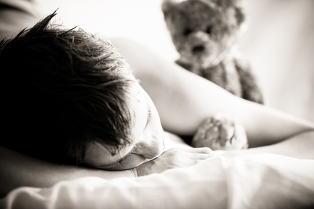 recuperating: Close Up of Young Teenage Boy Lying on Bed with Bare Shoulders with Head Resting on Hands with Comforting Teddy Bear in Background, in Sunny Bedroom in Morning - Concept Image with Sad and Lonely Feel Stock Photo