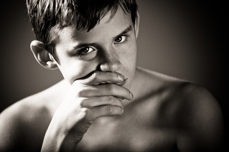 studious: Black and White Head and Shoulders Close Up of Young Shirtless Teenage Boy Staring at Camera with Serious Studious Expression and Hand Covering Mouth in Vignette Studio with Dark Background