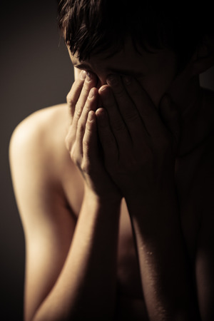 dejected: Waist Up of Young Shirtless Teenage Boy Holding Face in Hands in Studio with Dramatic Lighting and Dark Background - Upset Boy Crying or Upset and Hiding Face in Hands
