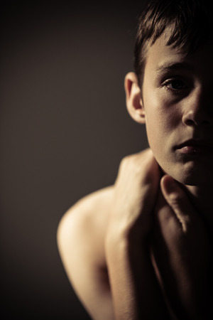 sombre: Head and Shoulders Close Up of Young Shirtless Teenage Boy Looking at Camera with Serious Expression and Holding Neck with Hands in Studio with Copy Space and Vignette Lighting