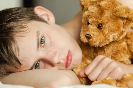 Head and Shoulders Close Up of Young Teenage Boy Lying on Bed and Snuggling with Soft Brown Teddy Bear and Staring at Camera with Sad or Serious Expression Standard-Bild