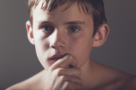 introspective: Head and Shoulder Portrait of Young Shirtless Teenage Boy Staring with Serious Expression Off Camera with Hand Resting on Chin in Studio with Dark Vignette Lighting and Copy Space