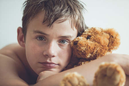 inscrutable: Head and Shoulders Close Up of Young Teenage Boy Lying on Bed and Snuggling with Soft Brown Teddy Bear and Staring at Camera with Serious Expression