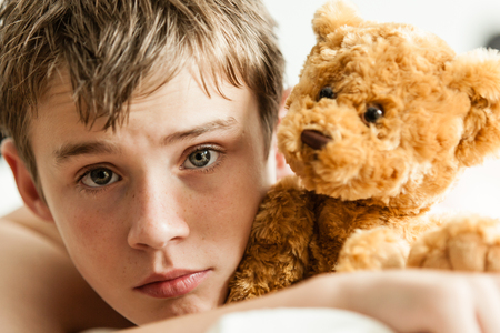 soulful eyes: Head and Shoulders Close Up of Young Teenage Boy Lying on Bed and Snuggling with Soft Brown Teddy Bear and Staring at Camera with Worried Expression
