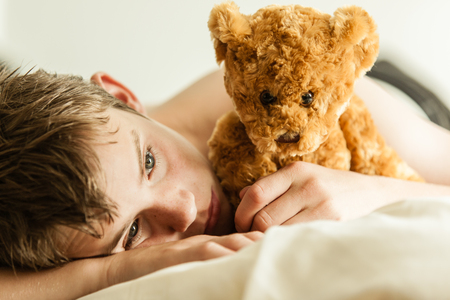 introspective: Close Up of Young Teenage Boy Feeling Sad and Lonely, Lying on Bed Snuggling with Soft Brown Teddy Bear - a Source of Comfort - in Room Filled with Sunlight