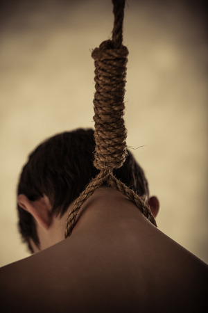 scandalous: Close Up Rear View of Young Male Hanging by Neck from Rope Tied into Noose - Suicide Concept Image in Studio with Vignette Lighting and Copy Space