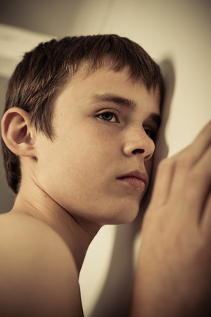 inscrutable: High Angle Close Up of Young Teenage Boy with Freckles, Shirtless and Looking Sad While Leaning Up Against White Wall in Room