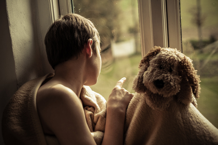 friendless: Young Teenage Boy Wrapped in Cozy Blanket Sitting in Window Sill with Stuffed Toy Dog and Peering Out Sadly at Yard Stock Photo