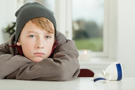 パーカーとキッチンにはテーブルの上の壊れたマグカップで腕にもたれながら悔恨探して防寒帽を身に着けている若い 10 代の少年のクローズ アップ