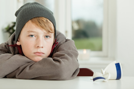 inscrutable: Close Up of Young Teenage Boy Wearing Hoodie and Winter Cap Looking Remorseful While Leaning on Arms in Kitchen with Broken Mug on Table