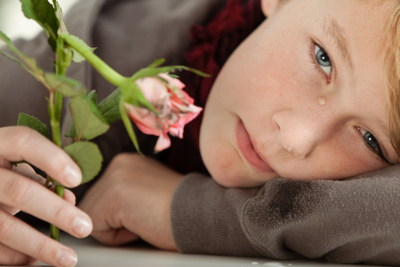 Close Up of Young Teenage Boy Resting Head on Table and Crying While Holding Broken Pink Rose in Hand