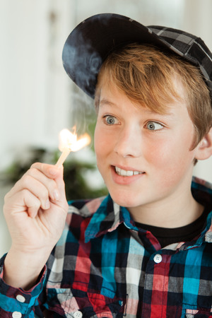 mesmerized: Head and Shoulders of Young Teenage Boy Wearing Baseball Cap and Plaid Shirt Looking Mesmerized by Flame of Lit Match Stock Photo