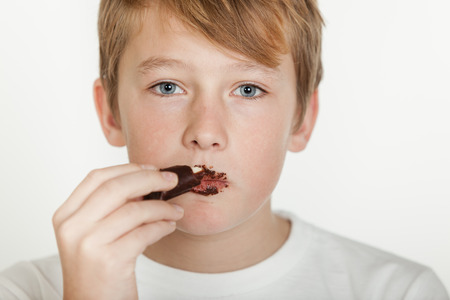 eat smeared: Head and Shoulders of Teenage Boy in White T-Shirt with Messy Face Eating Chocolate and Staring Seriously at Camera in front of White Background with Copy Space Stock Photo