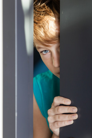 Single serious blond male teen in sleeveless blue shirt peeking from between gray metal door and wall