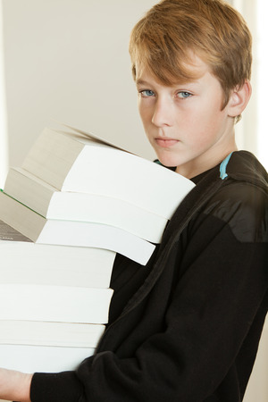 unmotivated: Boy in black hooded sweat shirt holding tall stack of thick books against a light colored background