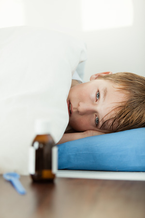 bedridden: Sick blond male child with fever laying down on blue pillow under thick white blanket with medicine bottle and spoon in front of him Stock Photo