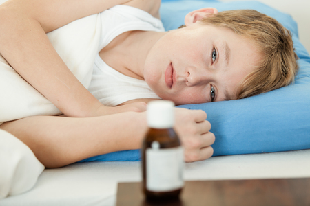 undershirt: Ill male child in undershirt and weak expression laying down on blue pillow next to medicine bottle on table Stock Photo