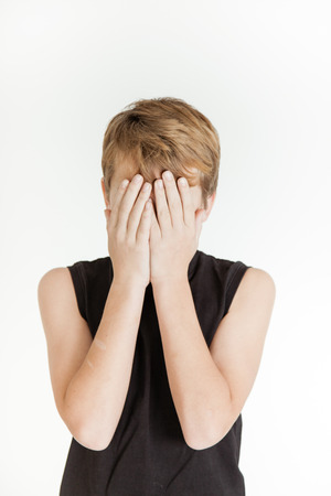 bashful: Frightened boy covering his face with both hands and wearing a black sleeveless shirt Stock Photo