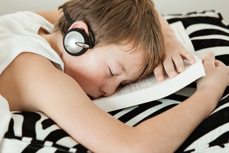 dozing: Exhausted young male student in undershirt with headphones asleep on top of textbook over striped black and white pillow Stock Photo