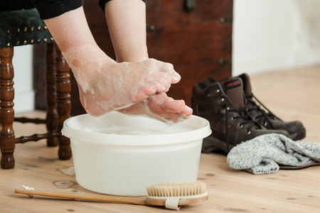 soaking: Close up on curled up toes over cold soapy water in plastic bowl and scrubbing brush beside shoes and socks Stock Photo