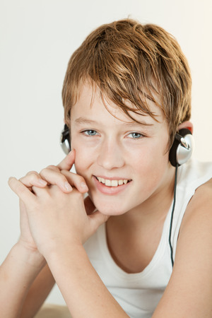 undershirt: Single cute boy in sleeveless undershirt smiling with folded hands near face while listening to headphones