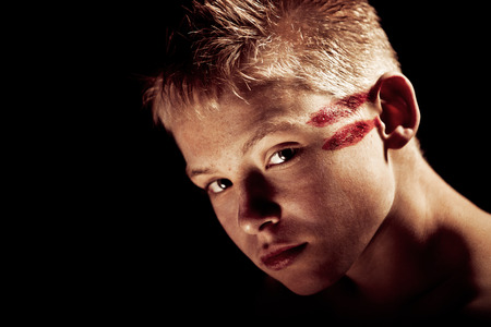 disobedient child: Dramatically lit head shot of serious young blond boy with red painted lines across side of head and copy space Stock Photo