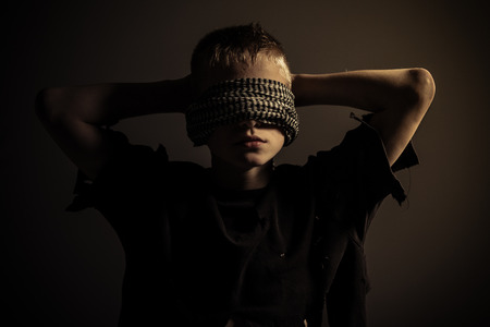 Front view on blond male child with thick blindfold around head and hands behind him in dimly lit room